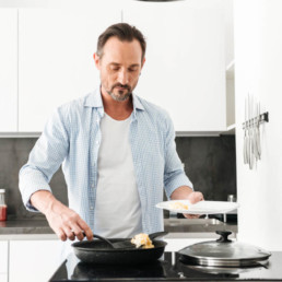 Confident mature man cooking breakfast