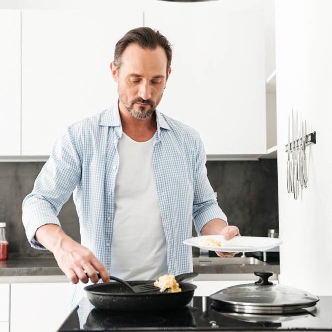 Confident mature man cooking breakfast