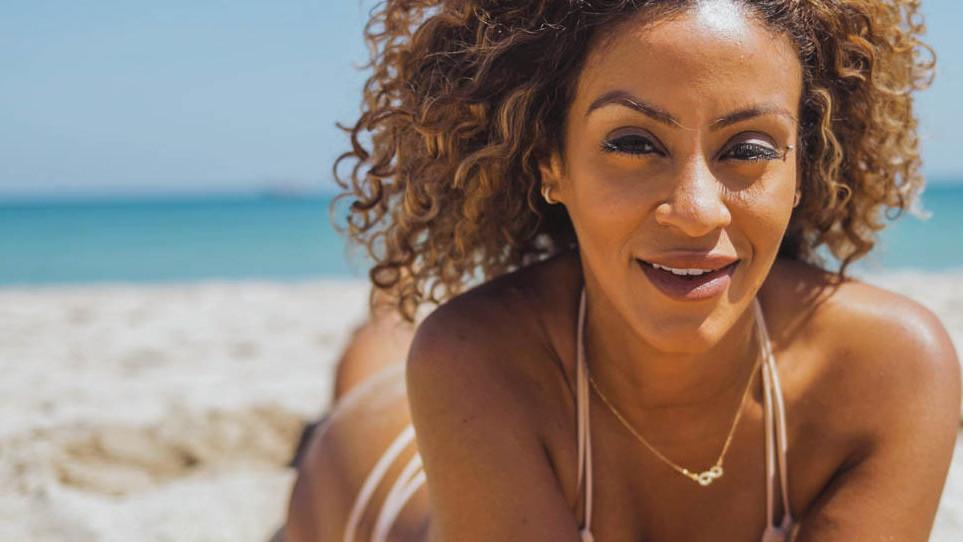 Pretty woman in bikini lying on beach